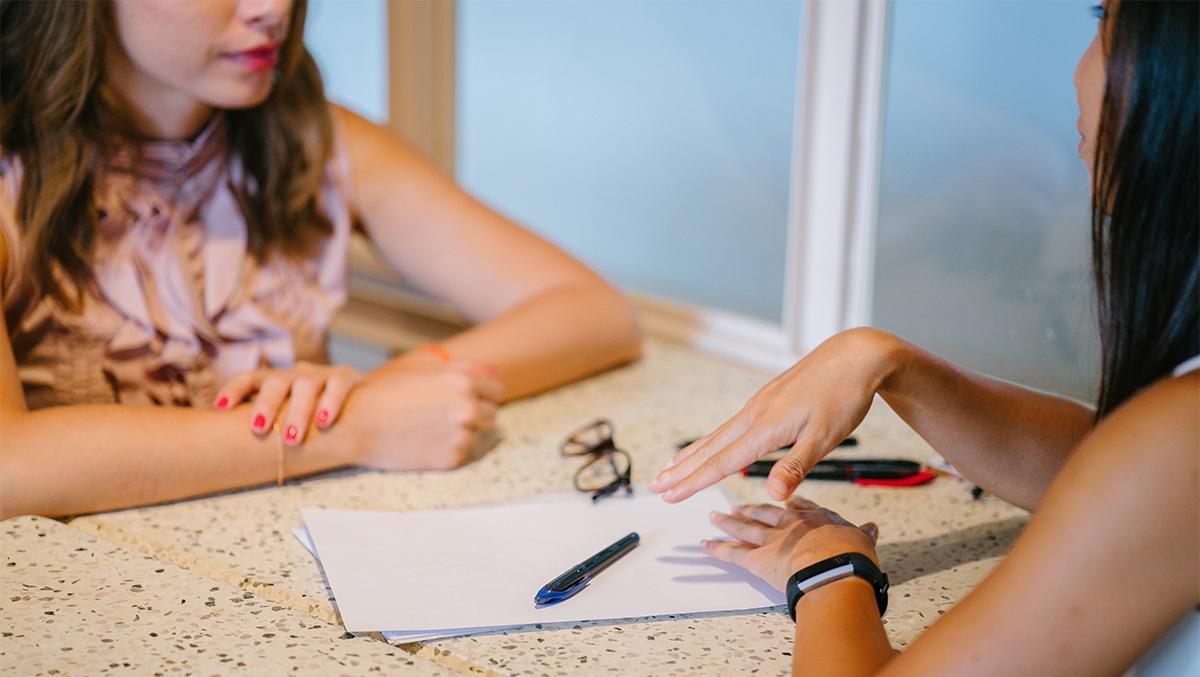 Två kvinnor sitter och pratar vid ett bord med några papper framför sig.