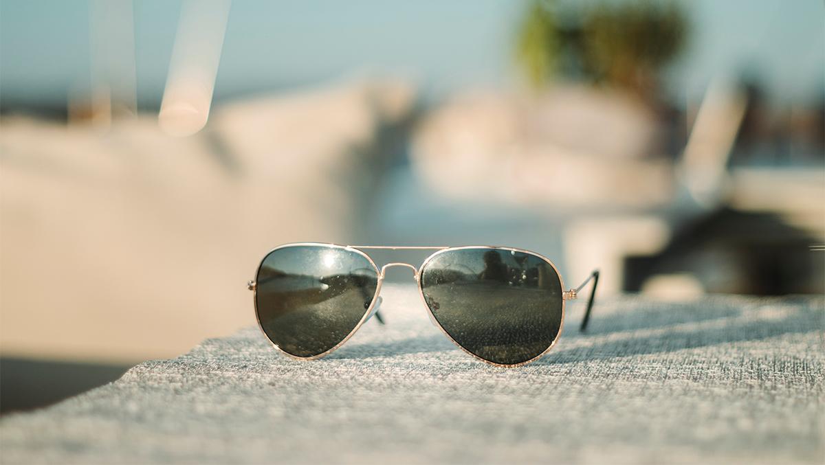 Solglasögon i pilotform som ligger på stenunderlag i solen