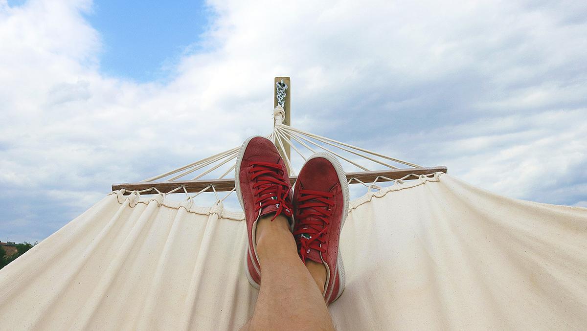 Korsade ben med röda skor i en hängmatta med himlen i bakgrunden.