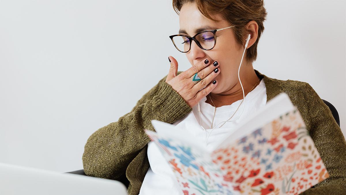 En gäspande kvinna sitter med en bärbar dator och ett anteckningsblock