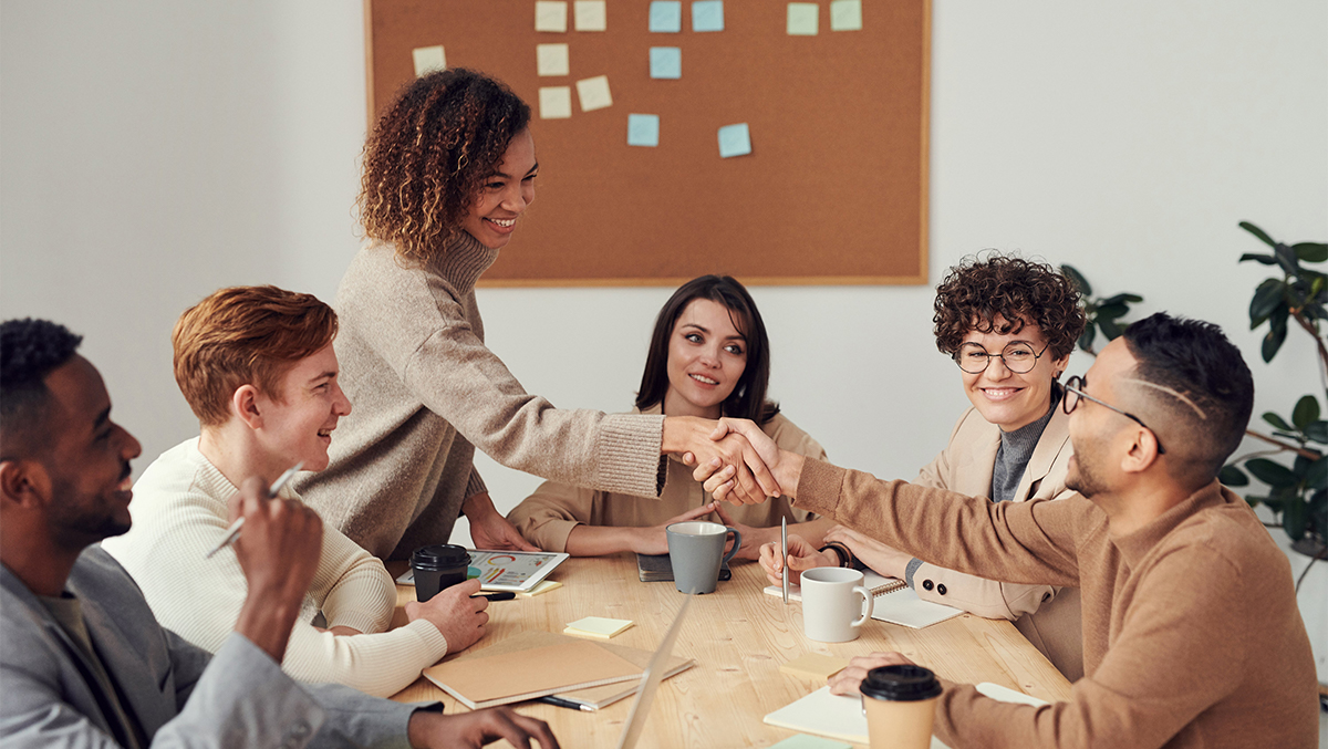 Kvinna skakar hand med en man över ett bord, kring bordet sitter fyra kollegor.