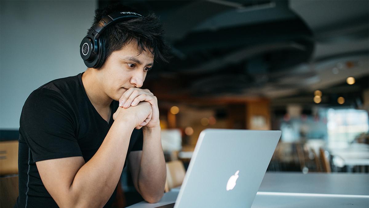 En man med hörlurar sitter vid en bärbar dator och ser fundersam ut.