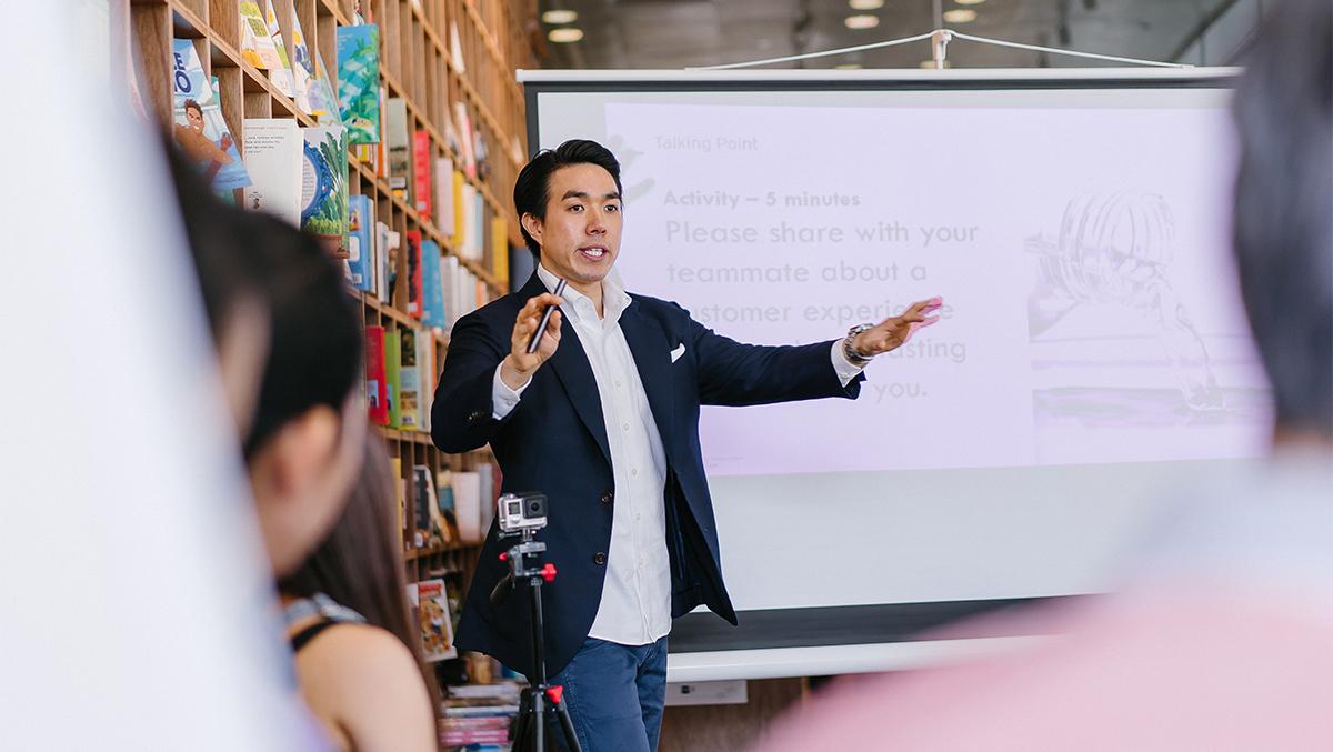 En man står framför en tavla och håller en presentation.