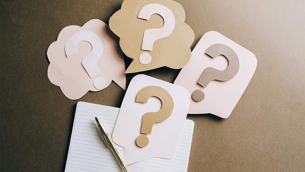 Ett anteckningsblock och en penna på ett bord tillsammans med tre frågetecken ovanför dem.