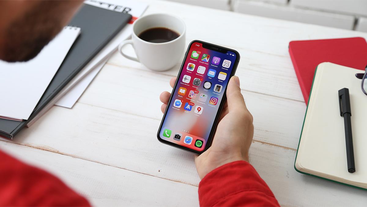 En man håller en smartphone i sin hand vid ett skrivbord.