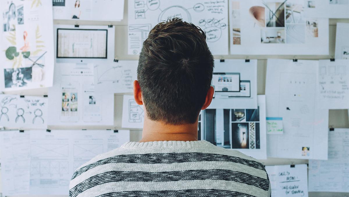 En person står och tittar på en tavla med många papper.