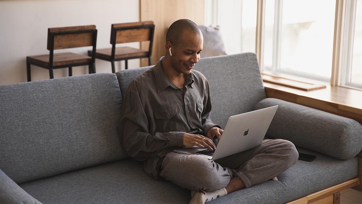 En man sitter i en soffa med en bärbar dator i knät